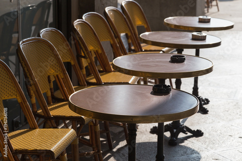 Fototapeta Row of cafe chairs and tables outside on terrace