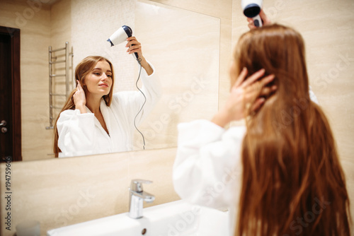 Woman drying hair with dryer in bathroom
