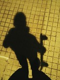 Shadow of a boy holding a skateboard.
