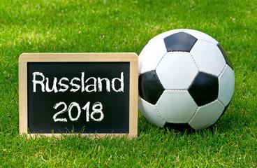 Russland 2018 - Fußball mit Kreidetafel und Text auf Spielfeld mit grünem Rasen