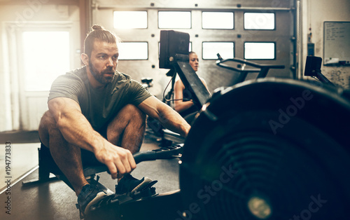 Fotobehang Fitness Fit man working out during a gym rowing machine class