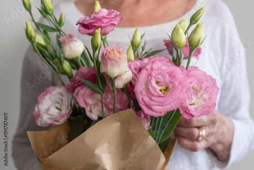 Close up of woman holding bouquet of pink lisianthus flowers wrapped close up of woman holding bouquet of pink lisianthus flowers wrapped in brown paper selective mightylinksfo