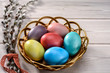 Traditional Easter  painted eggs prepared for the celebration of Easter are on the wooden table with willow branch