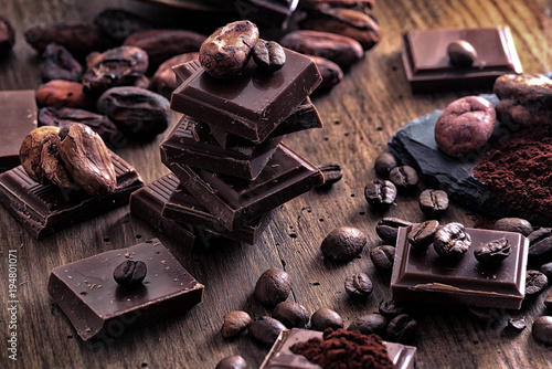 Broken dark chocolate, cocoa powder and coffee beans on a wooden table