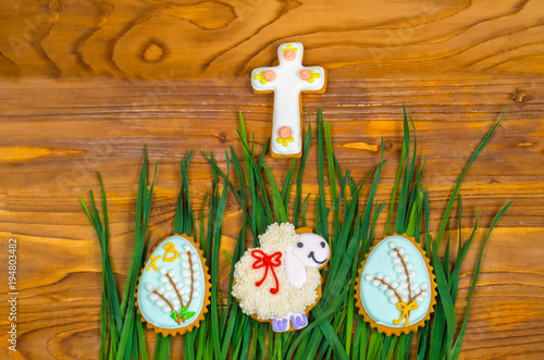 Easter cookies. Little Sheep and Easter eggs on green grass
