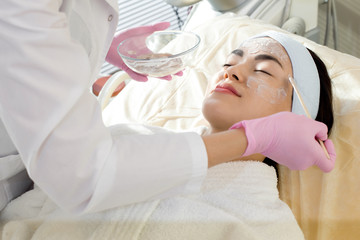 Beautiful young woman wearing headband and bathrobe lying on treatment table while unrecognizable beautician applying moisturizing mask on her face