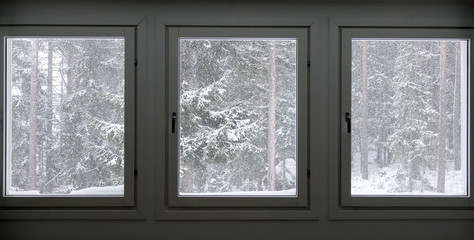 Three windows with a cold snow storm outside.