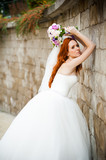 Beautiful red haired bride with wedding bouquet walking in the park near castle