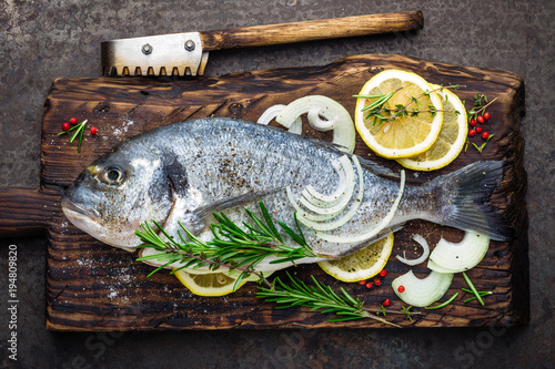 Fresh fish dorado with ingredients for cooking on wooden board. Raw sea bream or dorada fish on dark vintage metal background. Dietary food. Top view - 194809820
