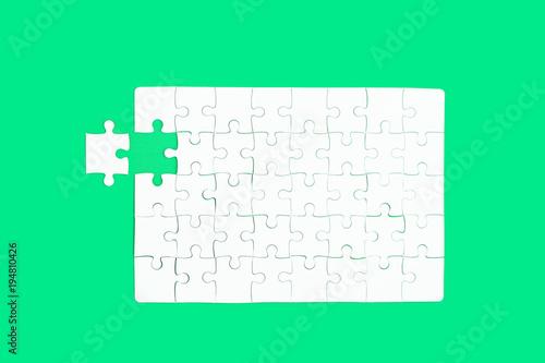 Leinwandbild Motiv White jigsaw of puzzle on green background.