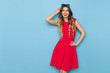 Beautiful Fashion Model In Red Dress Is Smiling And Looking Away