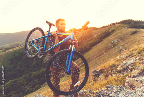 Jazda rowerem. młody człowiek z rowerem na charakter w górach