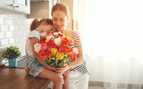 happy mother's day! child daughter   gives mother a bouquet of flowers to tulips