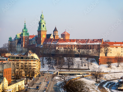 Fotobehang Krakau Krakow, Poland. Wawel Cathedral and castle in winter with snow, Vistula river bank and hotels. Aerioal view in sunset light.