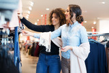 Two young girls look at clothing in store - 194824883