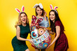 Easter. Happy Easter. Cheerful cute women holding big air balloon in form of egg, celebrating the holiday, having fun together.Isolated on yellow background.