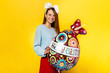 Easter. Happy Easter Day. Cute young woman wearing bunny ears holding egg shape balloon, looking at camera, celebrating the holiday. Dressed in blouse and skirt, isolated on yellow.