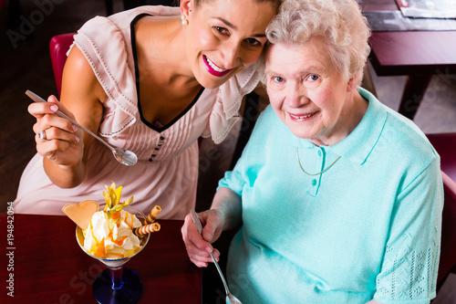 Fototapeta Senior woman and granddaughter having fun eating ice cream sundae in cafe