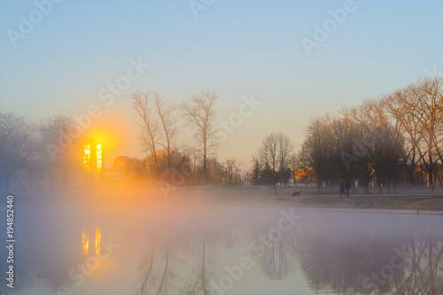 Dwaj mężczyźni we wczesnym mgłowym poranku chodzą po psach. Męskie sylwetki w gęstej ranek mgle na brzeg rzeki w miasto parku. Promienie słońca w odbiciu okien budynków przecinają mgłę