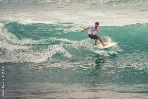 Fototapeta Surfer on Blue Ocean Wave, Bali, Indonesia. Riding in tube.