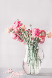 Pastel color ranunculus flowers bunch in glass vase on table, front view - 194857853