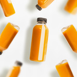 Yellow smoothie or juice bottles pattern on white background, top view, flat lay. Branding copy space - 194858482