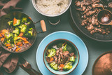 Healthy balanced nutrition dish in pots and bowls with beef meat, steamed vegetables and rice on table background with plate and cutlery, top view - 194861675