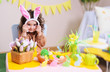 baby girl in rabbit ears sitting at table on background of Easter decor