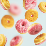 Falling or flying pink glazed doughnuts with sprinkles at pastel blue background , creative layout or pattern - 194869004