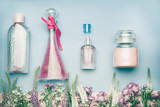 Natural cosmetic products. Jars and bottles with tonic , mist, perfume,cream ,tonic and micellar water on herbal leaves and wild flowers background, copy space for your text or branding , top view - 194869095