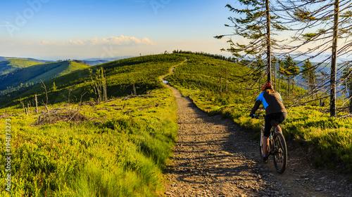 Kolarstwo górskie kolarstwo przy zmierzchem w lato gór lasu krajobrazie. Kobieta kolarstwo MTB przepływu szlak. Aktywność na świeżym powietrzu.