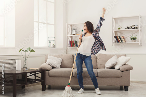 Foto Murales Happy woman cleaning home with mop and having fun