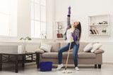 Happy woman cleaning home with mop and having fun - 194874659