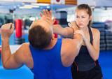 Fototapety Woman is training with man on the self-defense course in gym.