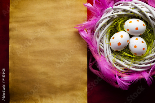 Three white Easter eggs in the nest and blank handmade paper sheet