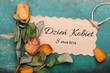 Polish International Women's Day card, with word: Women;s day. Dried orange roses and paper card on wooden background