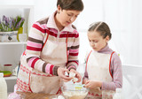 Mother and daughter cook at home. Kitchen interior, healthy food concept - 194889029