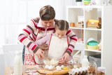 Mother and daughter cook at home. Kitchen interior, healthy food concept - 194889224