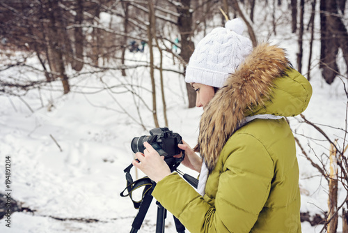 Woman Amateur photographer takes a winter landscape on the lake in the forest. copy space