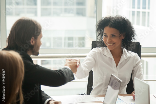 Staande foto Wanddecoratie met eigen foto Smiling african businesswoman and caucasian businessman shaking hands at meeting, black female boss handshaking welcoming new partner happy to start collaboration or making good first impression