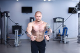 Young man training at gym with exercises . Young man
