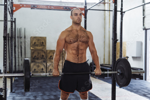 Fit male athlete exercising with heavy weights at training gym.