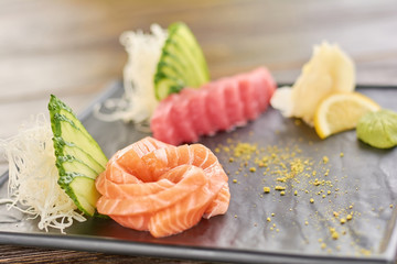 Raw salmon and tua sashimi. Sliced fresh tuna and salmon on japanese dish, focus on salmon.
