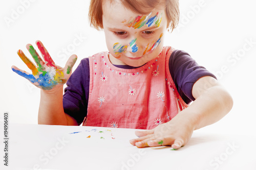 Child girl painting with colorful hands. ( people, childhood, drawing concept)