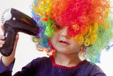 Humorous portrait of cute little girl drying her colorful curly hair with hairdryer.