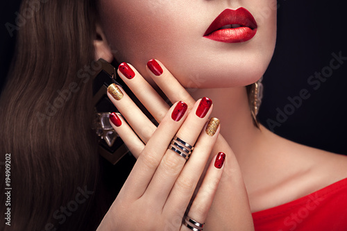 Aluminium Manicure Beautiful woman with perfect make-up and red and golden manicure wearing jewellery