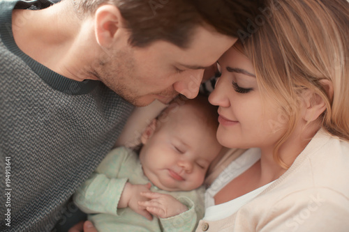 Portrait of young parents with sleeping baby