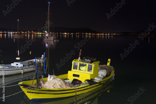 Small, wooden fishing boats with sailboats in the background in