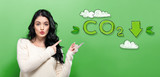 Reduce CO2 with young woman on a green background - 194923830