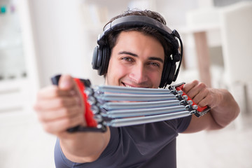 Man doing sports with resistance band and listening to music © Elnur